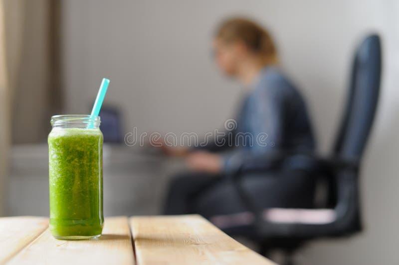 Groen monster smoothie Jonge vrouw als achtergrond met laptop stock foto's