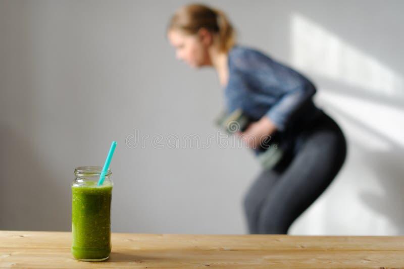 Groen monster smoothie Op de achtergrond is een vrouw bezet in royalty-vrije stock fotografie