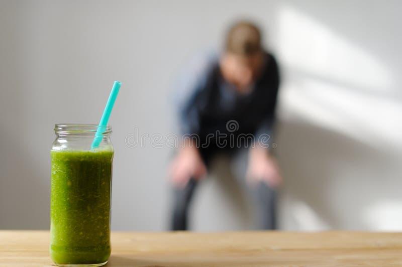 Groen monster smoothie Op de achtergrond is een vrouw bezet in royalty-vrije stock foto's