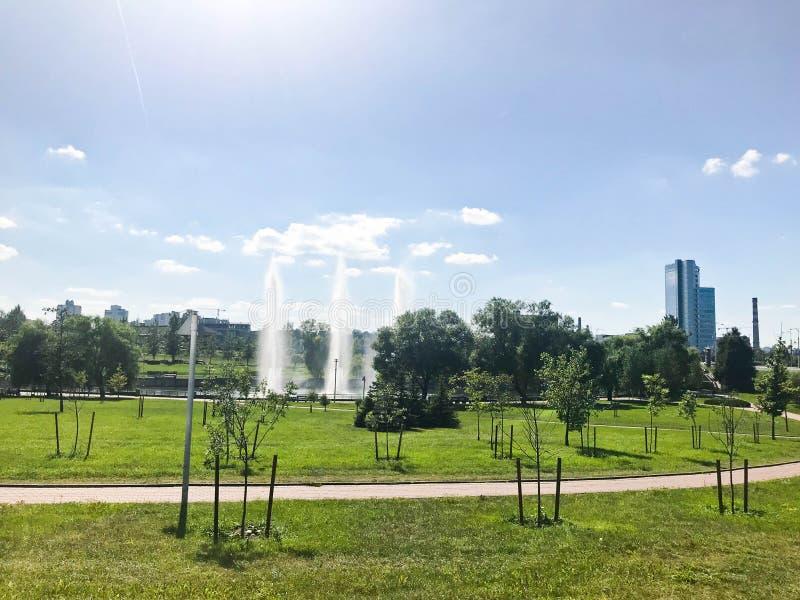 Groen mooi jong park in het centrum van een grote stad met fonteinen en zaailingen van kleine bomen tegen de achtergrond royalty-vrije stock afbeelding