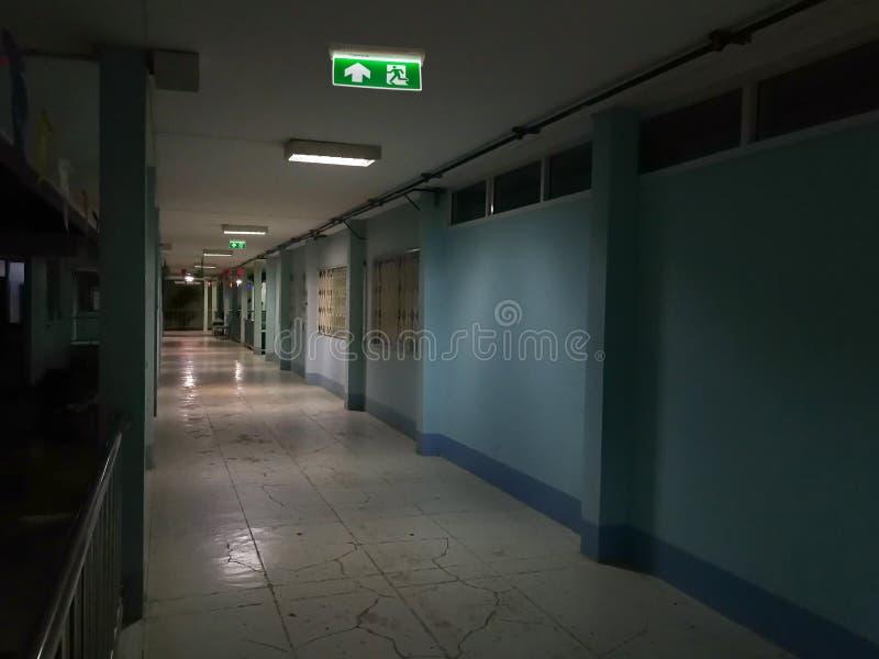 Groen nooduitgangteken in het ziekenhuis die de manier tonen om bij nacht te ontsnappen royalty-vrije stock fotografie
