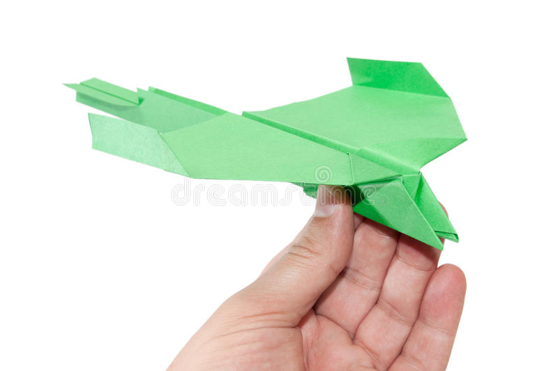 Groen origamivliegtuig in hand het vliegen stock fotografie