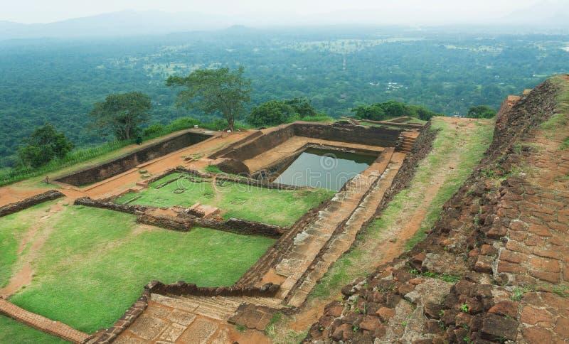 Groen plateau van bergstad Sigiriya met landelijk landschap, waterpool, ruïnes, bomen, Sri Lanka De erfenisplaats van Unesco stock foto