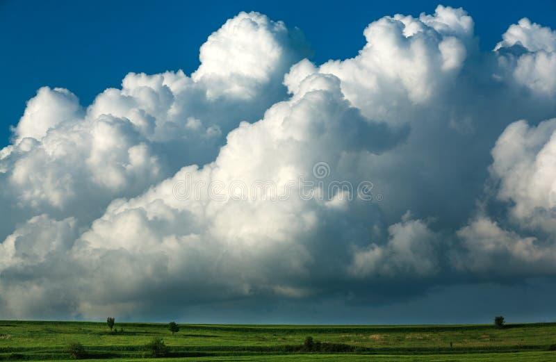 Groen weidenlandschap in plattelandsheuvels op indrukwekkende reusachtige wolken in hemel, schoonheid in aard royalty-vrije stock afbeelding