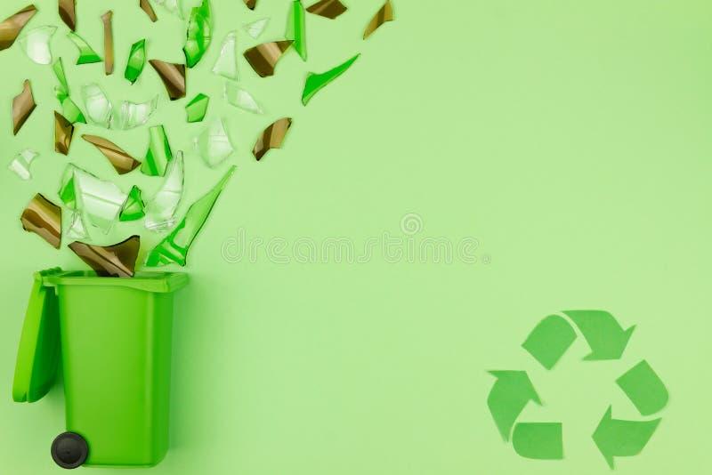 Groene afvalbak met verbrijzeld glas als symbool van afvalhergebruik en kringloopconcept royalty-vrije stock foto