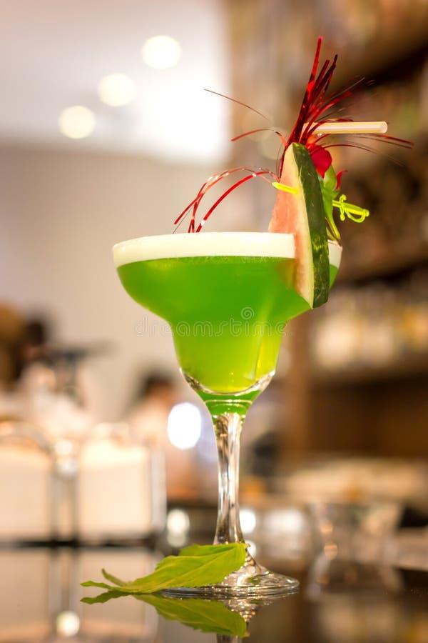 Groene alcoholische cocktail met munt in een glas van Margarita op een barteller stock foto