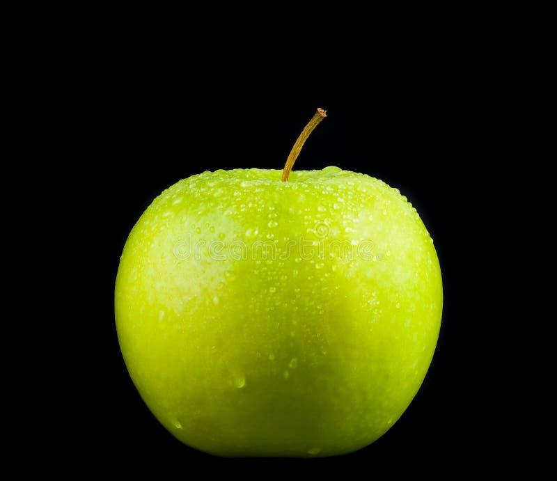 Groene appel met druppeltjes op zwarte achtergrond stock foto