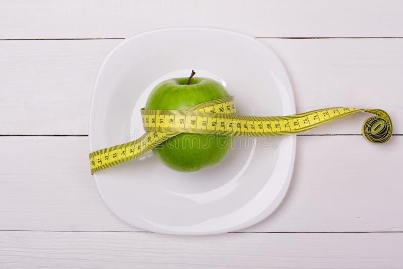 Groene appel met het meten van band op een plaat royalty-vrije stock fotografie