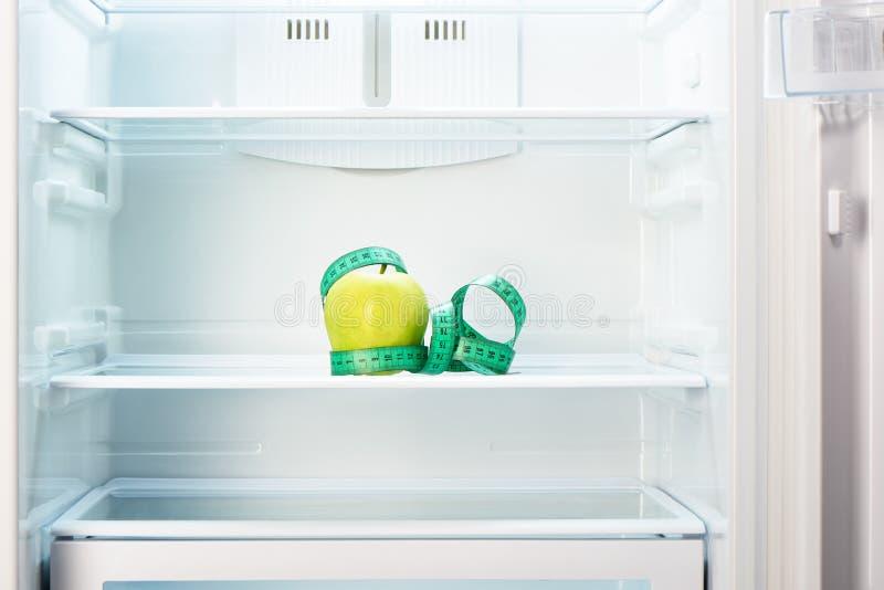 Groene appel met het meten van band op plank van open lege ijskast stock afbeelding