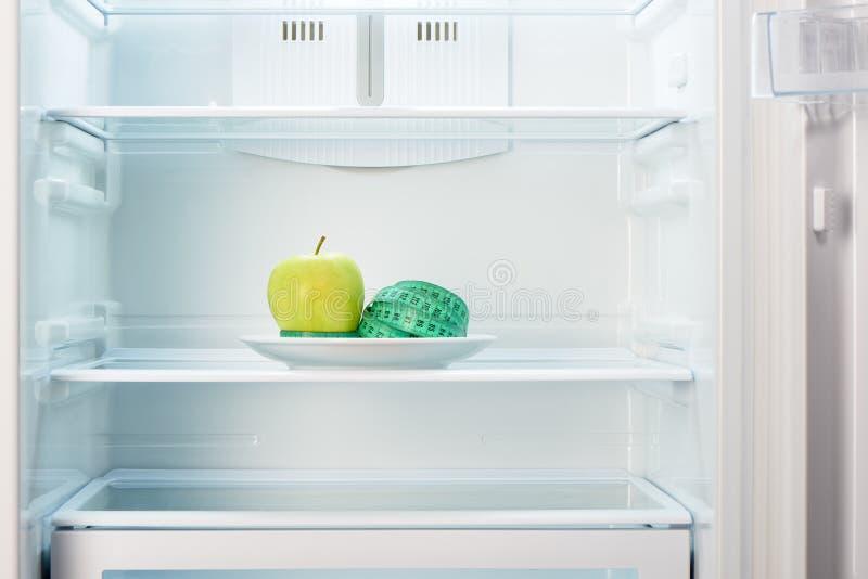 Groene appel met het meten van band op witte plaat in open lege ijskast stock afbeeldingen