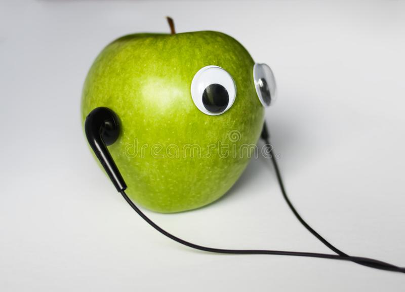 Groene appel met leuke ogen en hoofdtelefoons op witte achtergrond Conceptuele foto royalty-vrije stock foto's