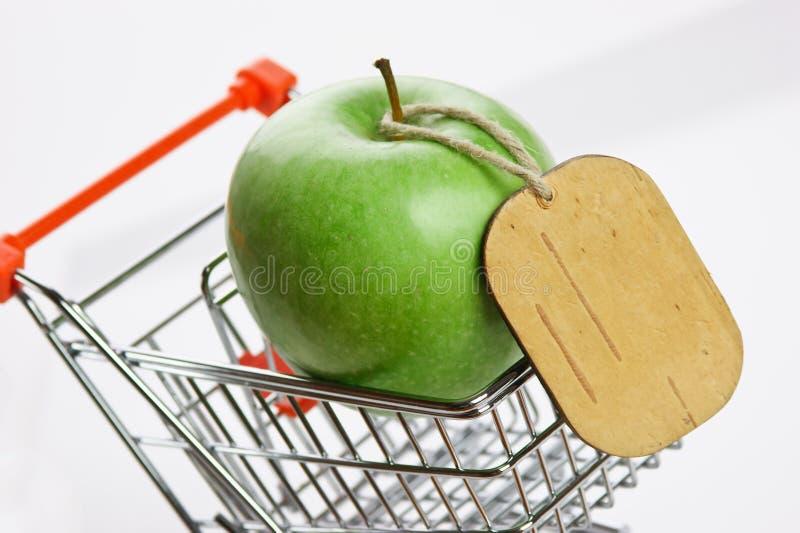Groene appel met markering in boodschappenwagentjes royalty-vrije stock afbeelding