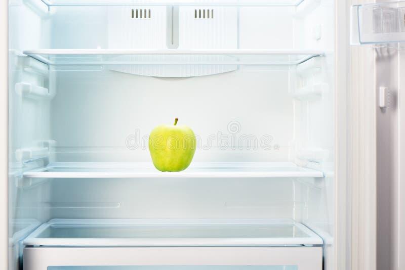 Groene appel op plank van open lege ijskast royalty-vrije stock foto