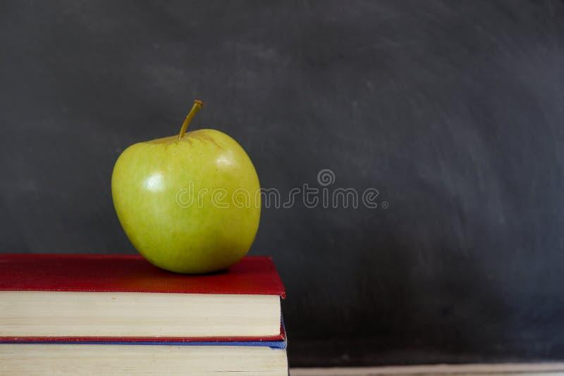 Groene appel op schoolhandboek stock foto
