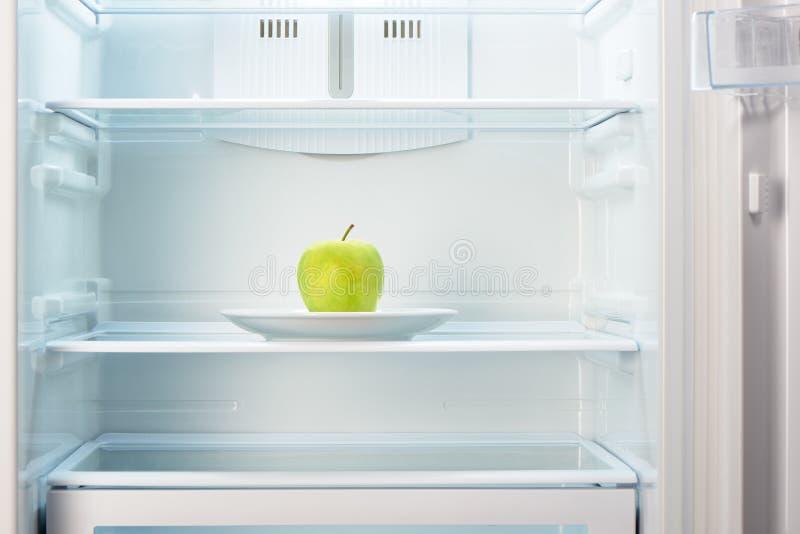 Groene appel op witte plaat in open lege ijskast stock foto's