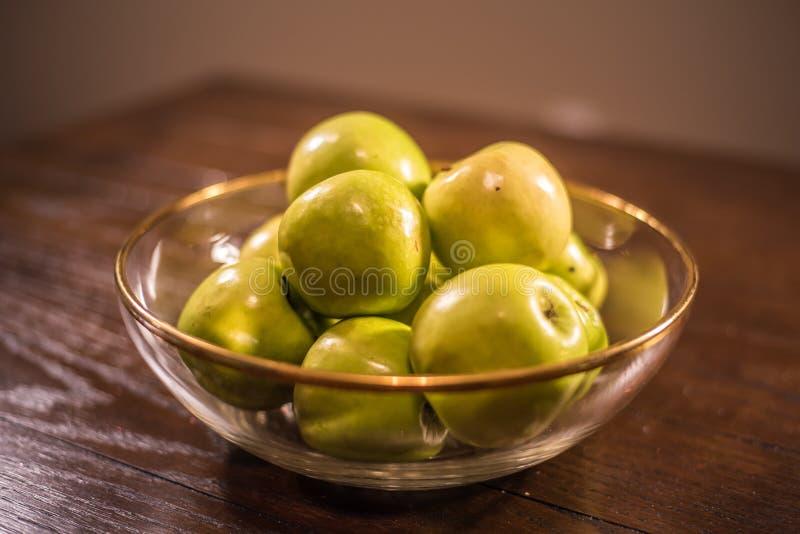 Groene appelen in duidelijke kom op lijst stock afbeeldingen