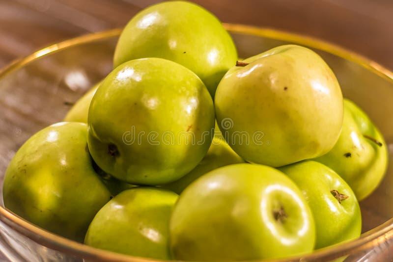Groene appelen in duidelijke kom op lijst stock afbeelding