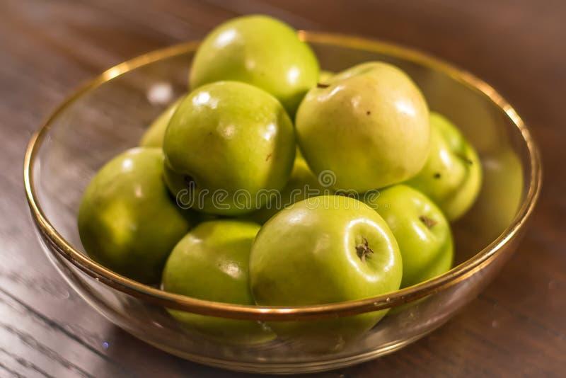 Groene appelen in duidelijke kom op lijst stock foto