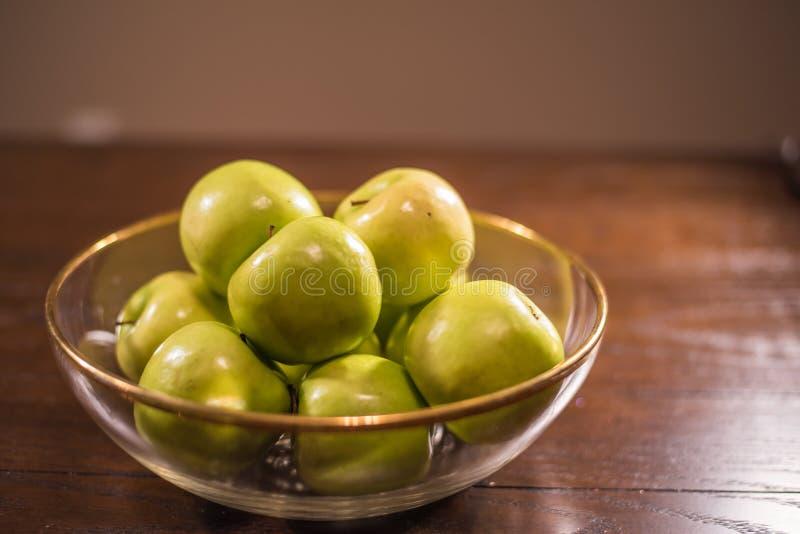 Groene appelen in duidelijke kom op lijst stock fotografie