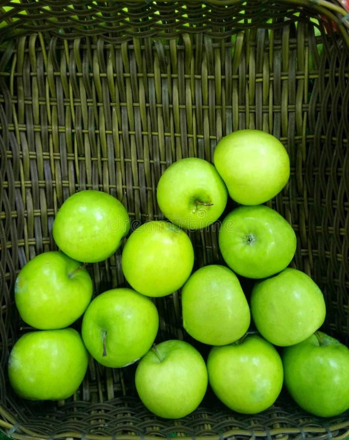 Groene appelen in een mand stock afbeeldingen