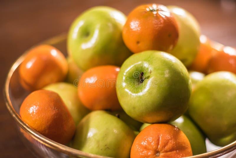 Groene appelen en sinaasappelen in duidelijke kom op lijst royalty-vrije stock foto