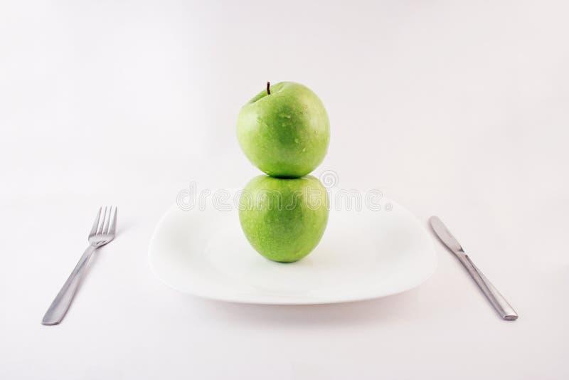 Groene appelen op een plaat stock afbeeldingen