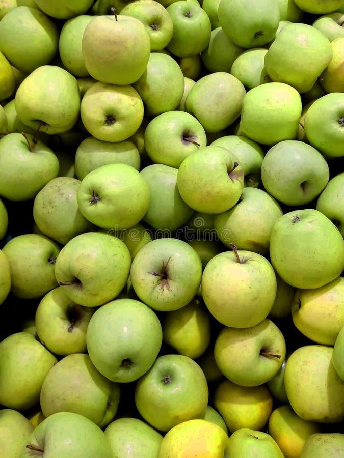 Groene appeltextuur: veel groene appelen Appelenopslag stock afbeelding