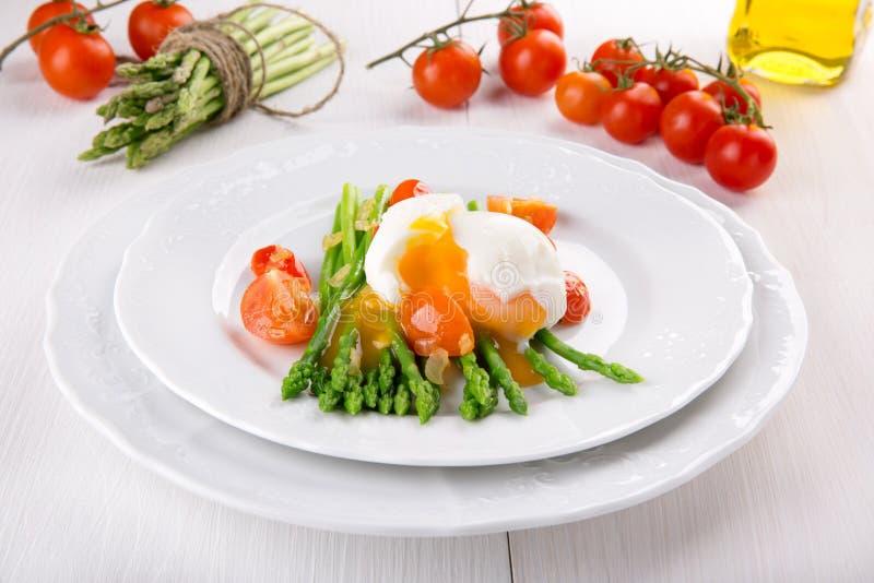 Groene aspergestammen met zacht-gekookte ei, tomaat en saus stock fotografie