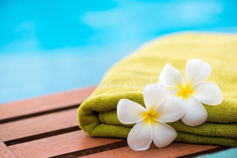 groene badstofhanddoek op chaise-longue dichte omhooggaand en twee bloemen stock afbeelding