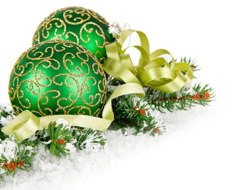 Groene ballen in sneeuw met takspar stock foto