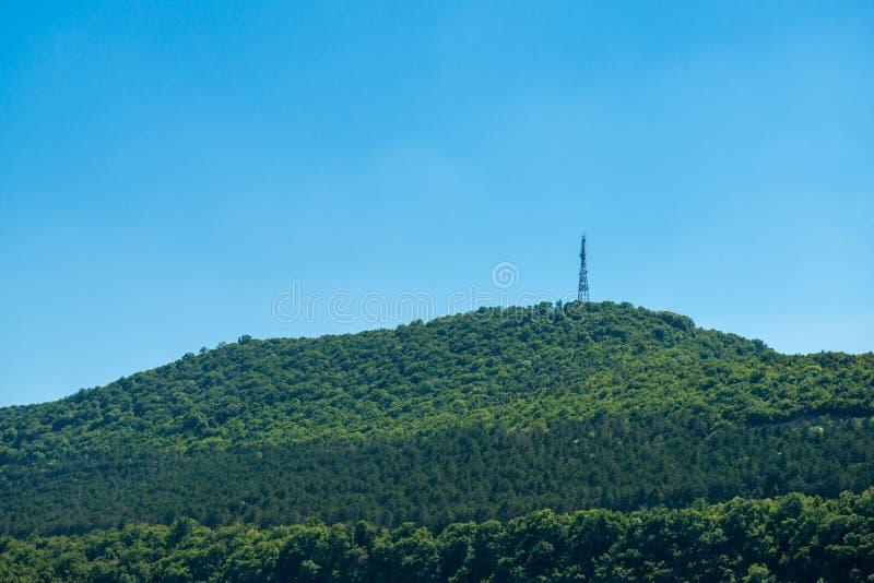 Groene berg naast overzees met radiotoren op bovenkant stock afbeeldingen