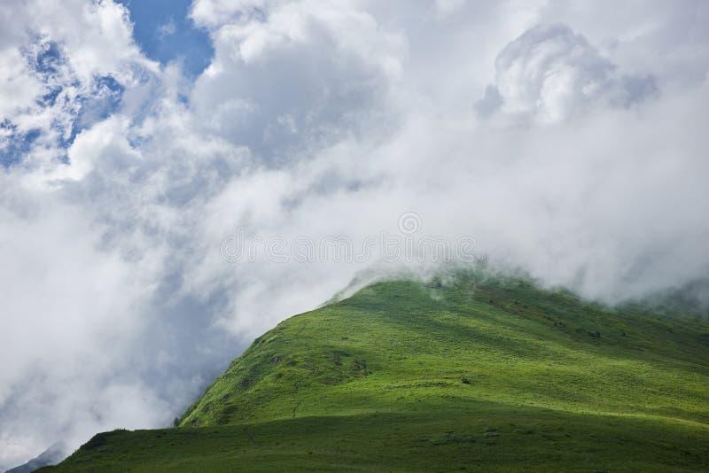 Groene bergen die in wolken worden gehuld stock afbeeldingen