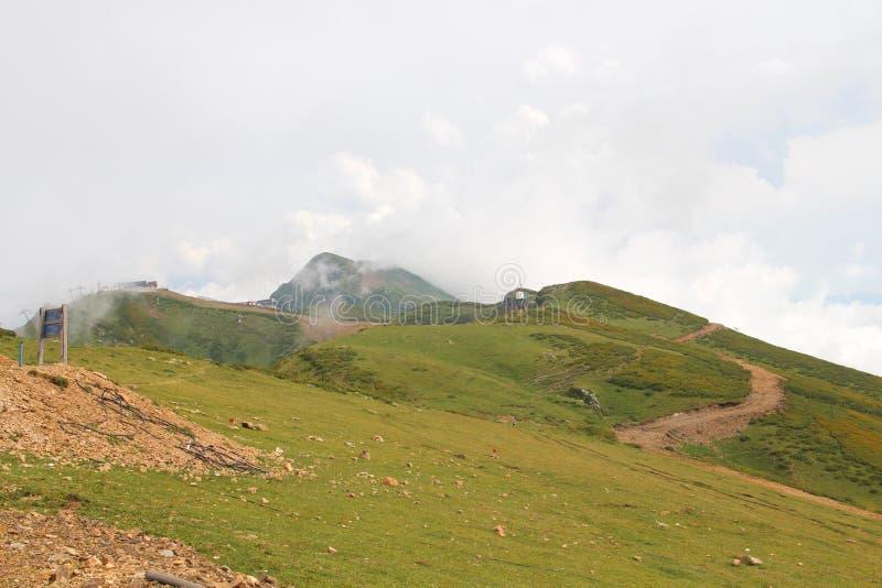 Groene bergen en weiden in de wolken stock afbeelding