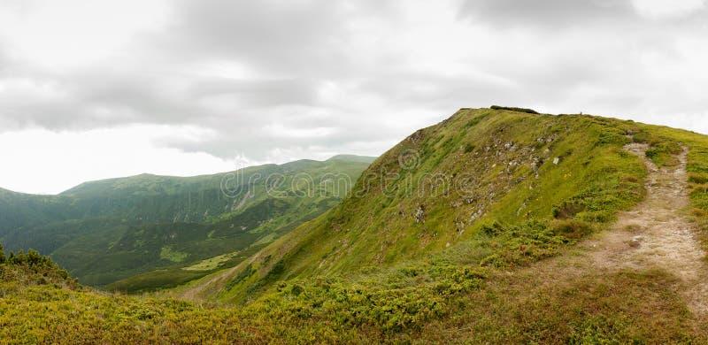 Groene bergheuvel met grijze wolken royalty-vrije stock foto