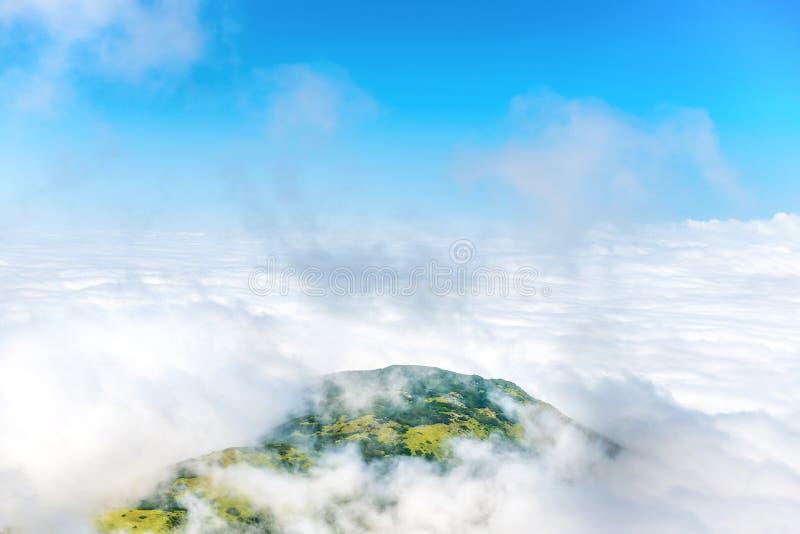 Groene bergpiek in witte wolken royalty-vrije stock afbeeldingen