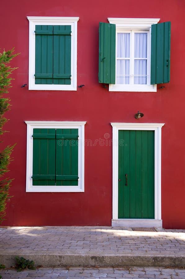 Groene blinden op een rode muur stock fotografie