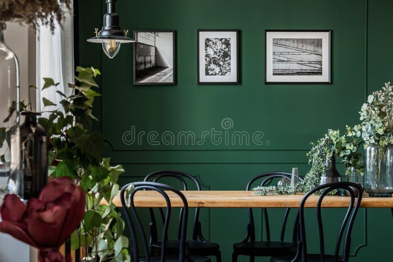 Groene bloemen in glasvaas op lange houten lijst met zwarte stoelen in elegante woonkamer stock afbeelding