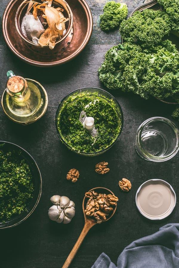 Groene boerenkoolpesto in mixer op de donkere rustieke achtergrond van de keukenlijst met ingrediënten, hoogste mening De voorber stock afbeelding