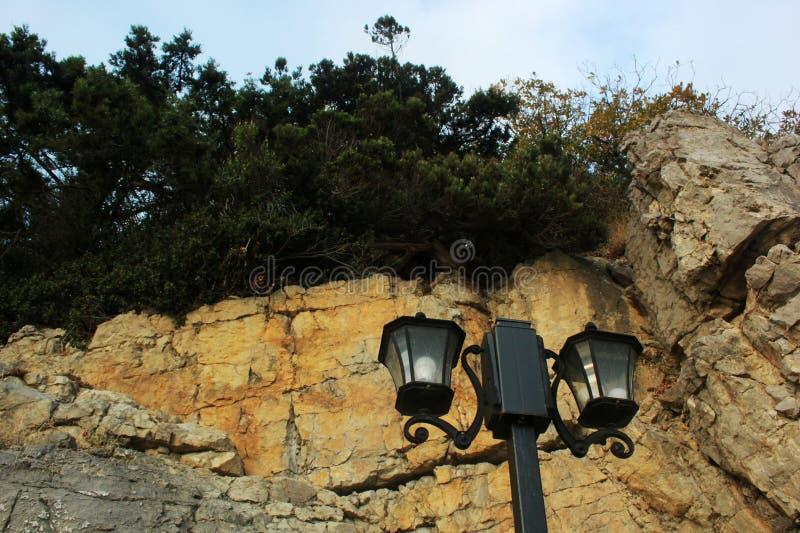 Groene bomen, aard van de Krim, een grote rots en een straatlantaarn, een kade en een steenkust, rotsen op de kust, lang zwart p stock foto