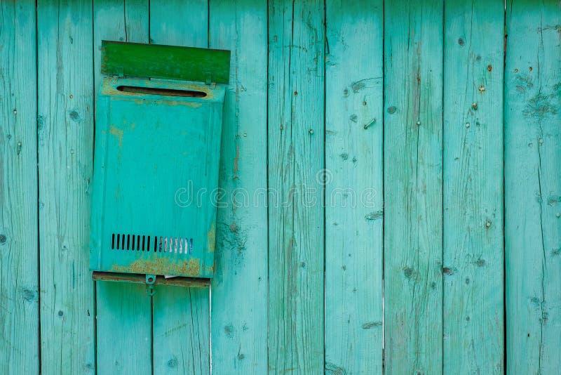 Groene brievenbus op een houten houten omheining stock foto's