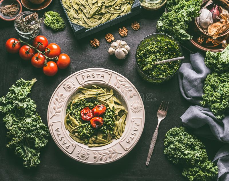 Groene deegwaren met ruwe boerenkoolpesto en geroosterde tomaten in plaat met vork op keukenlijst met ingrediënten Veganistvoedse stock foto