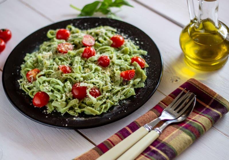 Groene deegwaren met tomaten en parmezaanse kaaskaas Witte achtergrond royalty-vrije stock afbeelding