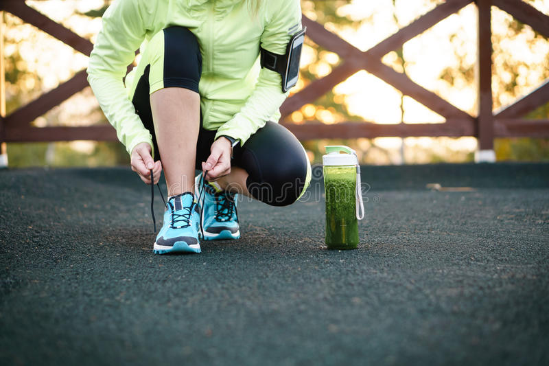 Groene detox smoothie kop en vrouw die loopschoenen rijgen vóór w stock foto's