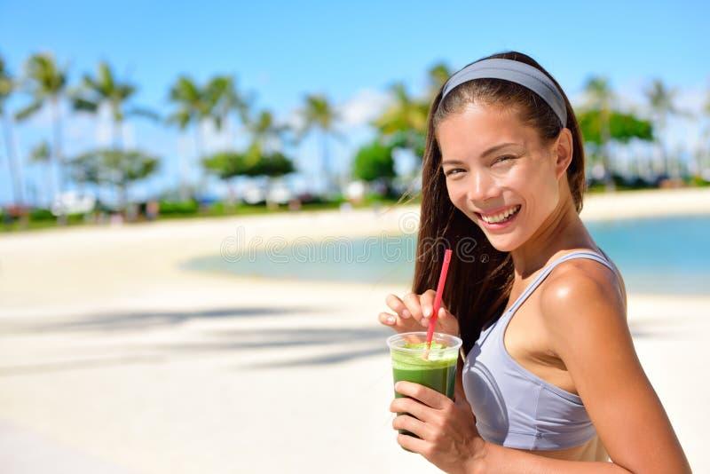 Groene detox smoothie - vrouw het drinken groenten stock afbeelding