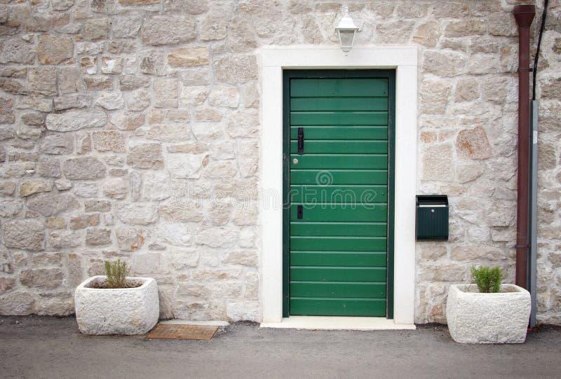 Groene deur in oud steenhuis stock fotografie