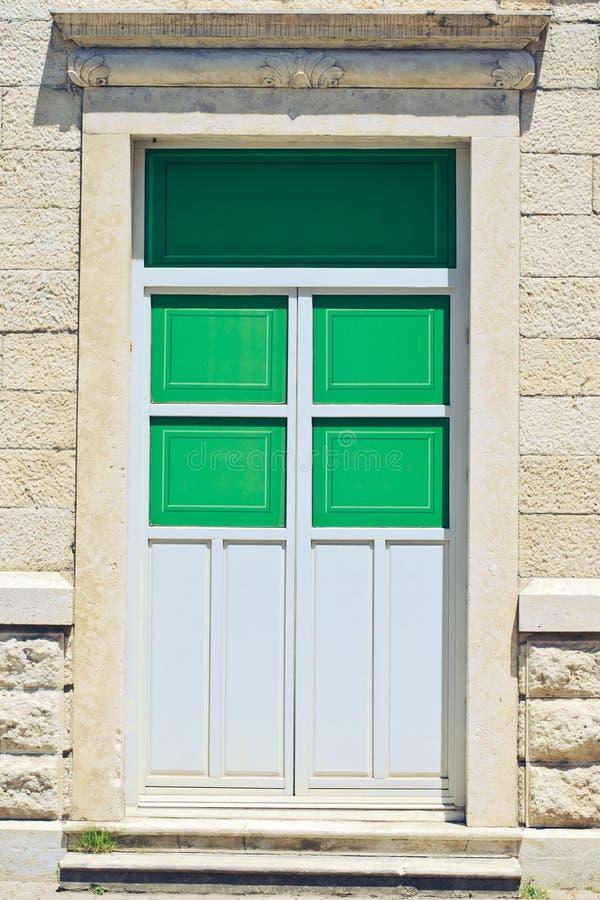 Groene deur tegen een oude muur stock foto's