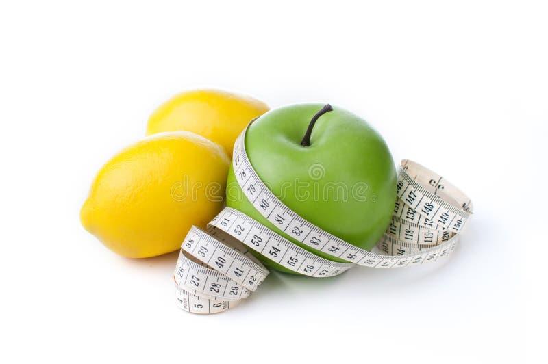 Groene die appel en citroen met het meten van band op witte achtergrond wordt geïsoleerd royalty-vrije stock fotografie
