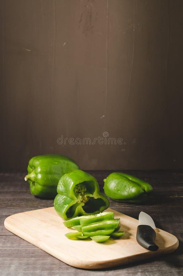 groene die paprika op een houten raads Snijdende peper wordt gesneden op een houten scherpe raad met mes op een donkere achtergro stock foto