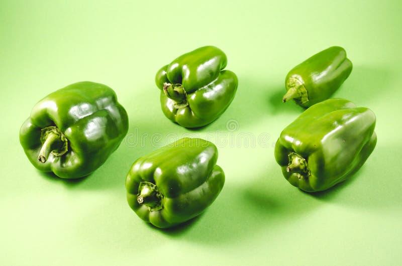 Groene die paprikapeper op een groene achtergrond/een Hoop van Verse Groene paprikapeper wordt geïsoleerd op groen royalty-vrije stock afbeeldingen