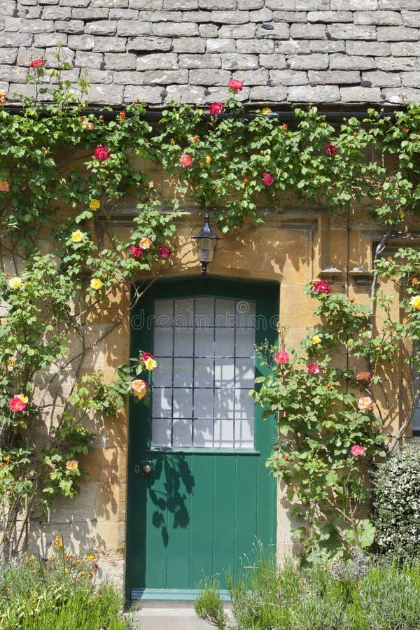Groene die plattelandshuisjedeuren door rode rozen worden omringd te beklimmen stock foto's